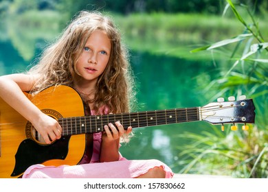 Close up portrait of young guitar student playing spanish guitar at lake.