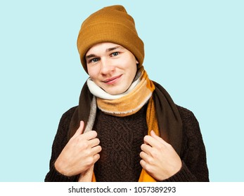 Close up portrait of young guy in sweaer and hat hiding his neck in scarf. Isolated on light blue background.