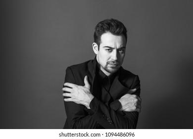 Close up portrait of a young handsome man in a suit, arms crossed on the chest, looking at the camera, against plain studio background