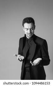 Close up portrait of a young handsome man in a black suit, standing, seriously looking at his hands while explaining something, against plain studio background