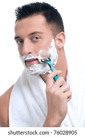 Close up portrait of young handsome man face with perfect skin shaving with foam.