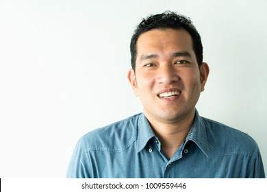 A close up portrait of young happy cheerful young man in checkered shirt in front of white background.
