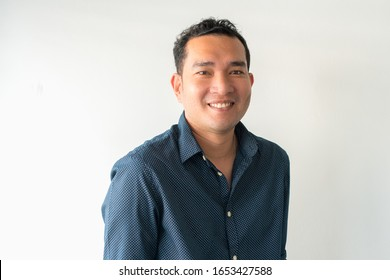 A close up portrait of young happy cheerful young man in shirt on white background.