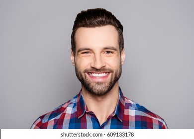 A close up portrait of young happy cheerful young man in checkered shirt in front of gray background.