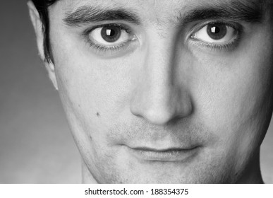 close up portrait of a young happy man, black and white studio shot