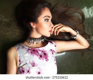 Close up portrait of young happy smiling brunette woman laying and enjoy her vacation in summer dress with flowers,wear bright stylish jeweler and accessories.Summer outdoor look,red lips,summer dress