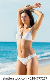 Close up portrait of young healthy woman in white bikini on beach. Muscular built female with attractive slim body.