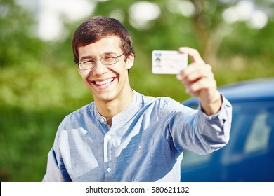 Close up portrait of young hispanic man wearing glasses and blue denim shirt holding out his driving license and smiling against car outdoors - new drivers concept