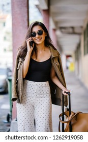 Close up portrait of a young Indian Asian socialite smiling as she talks on her smartphone. She is beautiful and stylish and is pulling a luggage bag with her.