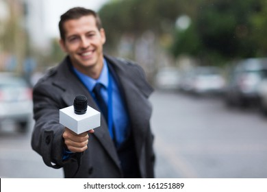 close up portrait of young journalist giving microphone