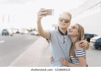 Close up portrait of a young loving stylish hipster couple have fun outdoor in city street and doing selfie