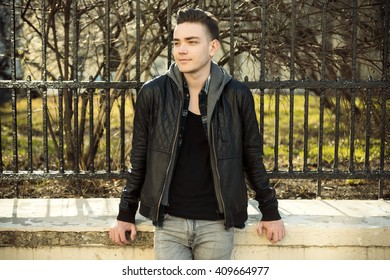 Close up portrait of young man in city park at sunny weather