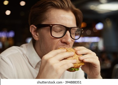 Close up portrait young man in glasses eating traditional burger in bar