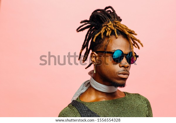 Close up portrait of a young man in green with dreadlocks and blue sunglasses, isolated on pink
