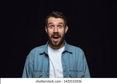 Close up portrait of young man isolated on black studio background. Photoshot of real emotions of male model. Wondering, exciting and astonished. Facial expression, human emotions concept.