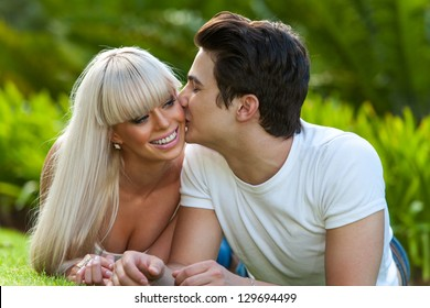 Close up portrait of young man kissing his girlfriend on cheek outdoors.