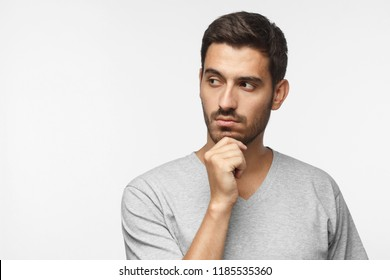 Close up portrait of young man looking left, holding chin as if thinking of something, trying to solve some problem, copy space for text