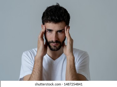 Close up portrait of a young man looking worried and thoughtful suffering from migraines in great pain. Isolated on neutral background. In facial expressions and emotions and heath care concept.