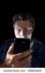 close up portrait of young man looking intensively to mobile phone screen with blue eyes wide open isolated on black background on dark edgy lighting scheme in addiction to internet technology
