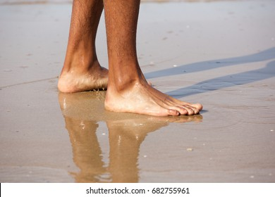 Close up portrait of young man standing with bare feet on beach