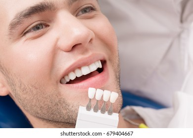 Close up portrait of Young men in dentist chair, Check and select the color of the teeth. Dentist makes the process of treatment in dental clinic office.Dentist