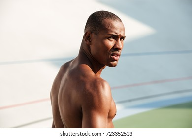 Close up portrait of a young muscular sportsman looking at camera while standing on a track field outdoors