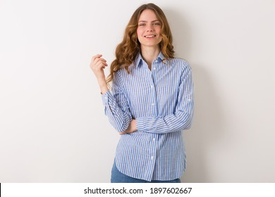 close up portrait of young natural pretty woman with curly haistyle, blond hair, student age, wearing blue striped shirt, isolated on white background, looking in camera