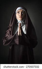 Close up portrait of young nun. Nun is praying. Photo on black background.