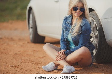 close up portrait of Young pretty blonde lady with a modern luxury car
