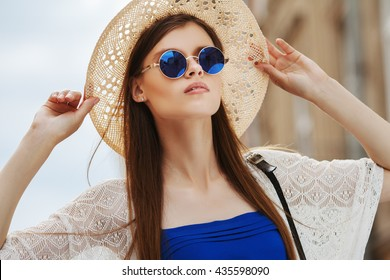 Close up portrait of young pretty lady posing on street. Model wearing stylish round blue sunglasses & straw hat. Girl looking up. Sunny day. Female fashion. City lifestyle. Copy space for text