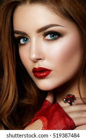 Close up portrait of young red-haired woman wearing red lips with glitters and brown smokey eyes. Perfect eyebrows. Modern fashion make up. Studio shot