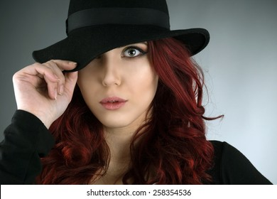 Close up portrait of young redhead posing with a hat isolated over gray background