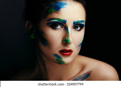 Close up portrait of young sensitive woman, posing with colorful paint brush strokes on her face and looking at camera