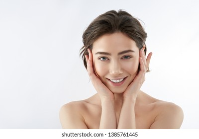 Close up portrait of young smiling naked brunette lady with nude make-up putting her hands around face. Isolated on white with copy space on left