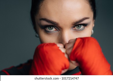 Close up portrait of a young sportswoman. Pretty female brunete boxer. Healthy lifestyle concept. Girl fighter. Woman's day