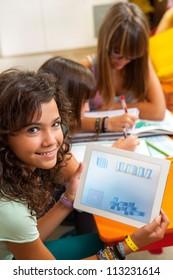 Close up portrait of young student at desk showing  homework on digital tablet.