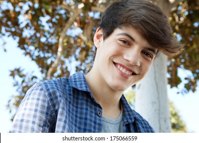 Close up portrait of a young student teenager boy near a tree, smiling joyfully at the camera during a sunny day out. Outdoors lifestyle.