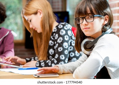 Close up portrait of young student together with friends at desk.