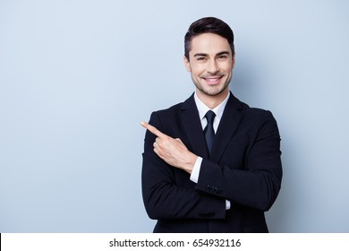 Close up portrait of young successful brunete  stock-market broker guy on the pure light blue background, he is smiling, wearing suit with tie and is pointing on a copyspace with his finger
