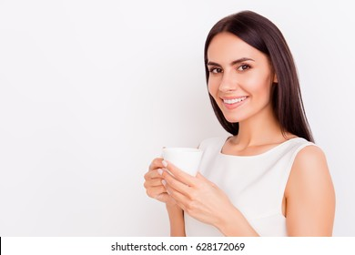 Close up portrait of young successful businesslady on a coffee break, she is resting and enjoying the drink. Woman is on a white background, she is smiling