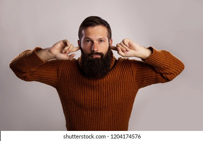 Close up portrait, young thick beard man in warm knitted sweater, covering closed ears, annoyed by loud noise or ignoring someone, isolated gray background. Negative human emotion