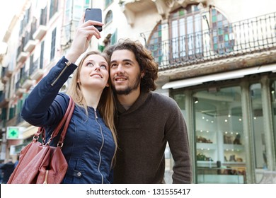 Close up portrait of a young tourist couple visiting a destination city and taking pictures of themselves while on vacation in Europe.