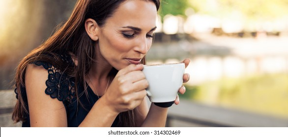 Close up portrait of young woman with an aromatic coffee in hands. Female drinking coffee at cafe.