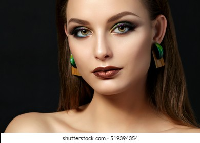 Close up portrait of young woman with brown lips and green smokey eyes over black background. Perfect eyebrows. Modern fashion make up. Studio shot