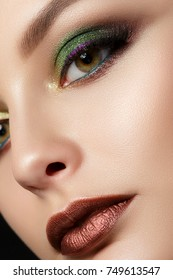 Close up portrait of young woman with brown lips and green smokey eyes. Perfect eyebrows. Modern fashion make up. Studio shot