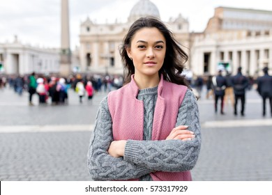 Close up portrait of young woman in the city. She looks stylish and confident and smiles to the camera.