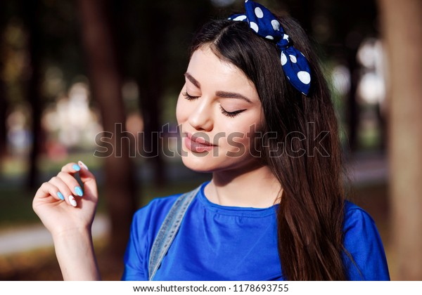 Close up portrait of young woman with closed eyes showing make up. Woman is wearing headband in her hair.