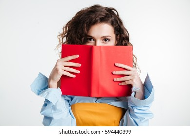 Close up portrait of a young woman covering her mouth with book isolated on the white background