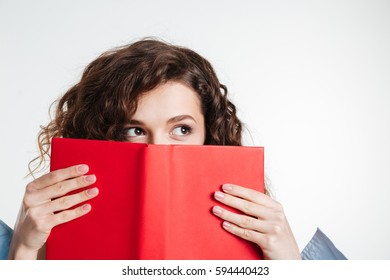 Close up portrait of a young woman covering her mouth with book and looking away isolated on the white background