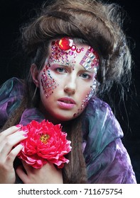 Close up Portrait of young woman in creative image  with big flowers.